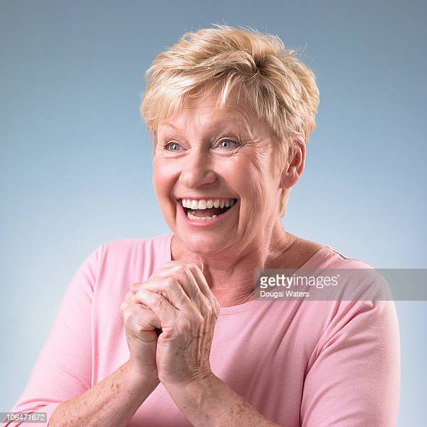 senior woman with hands clasped.