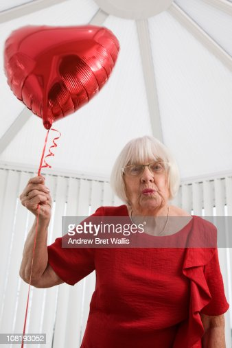 senior woman with heart balloon, blowing a kiss : Stock Photo
