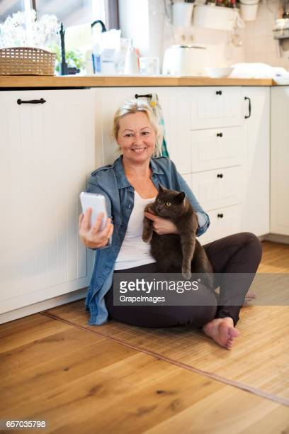 Senior woman with her cat at home taking selfie.