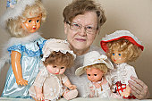 A senior woman with her collection of old-fashioned dolls