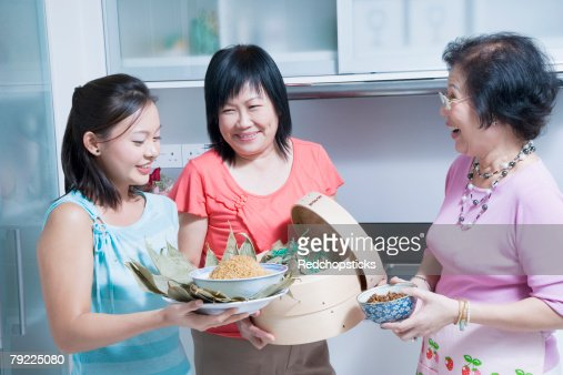 Senior woman with her daughter and granddaughter in a kitchen : Stock Photo