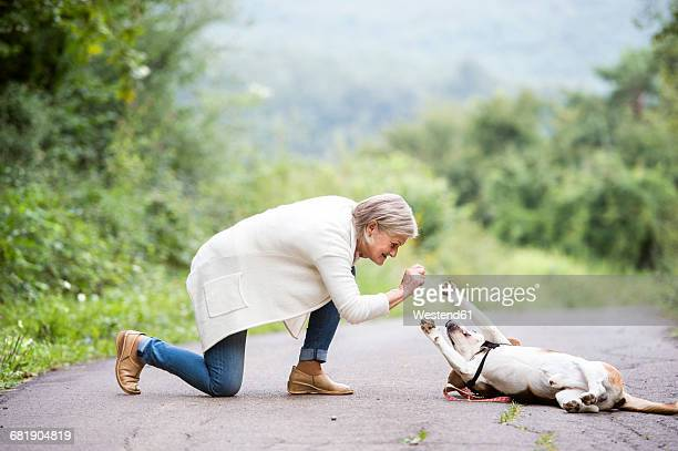 Senior woman with her dog in nature