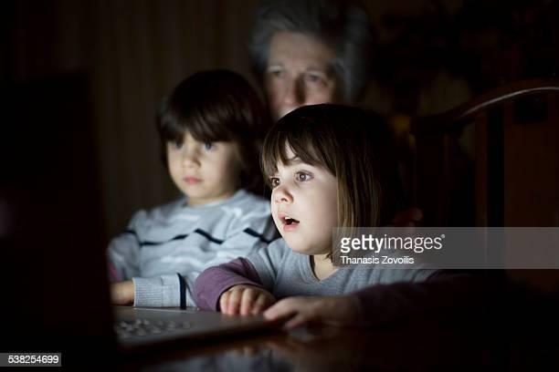Senior woman with her grandchildren using a laptop