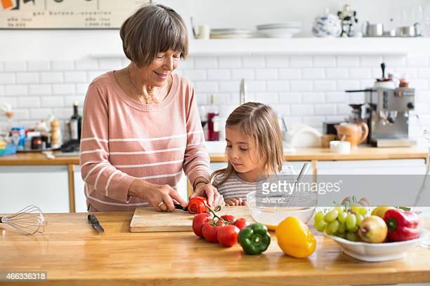 Femme âgée avec sa petite-fille couper les légumes dans la cuisine