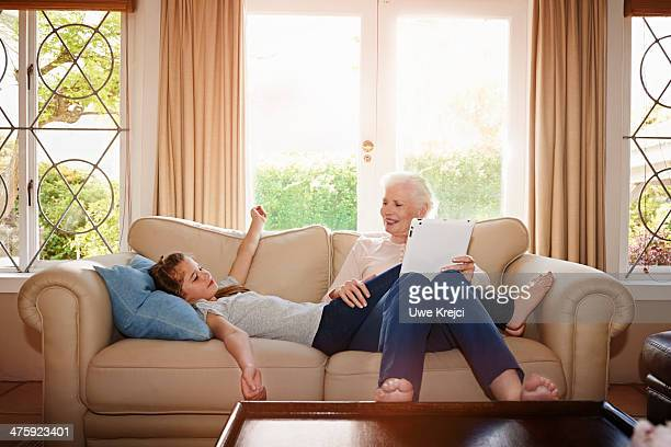 Senior woman with her granddaughter on couch