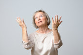 Senior woman with her hands up to the sky, standing with eyes closed on plain grey background