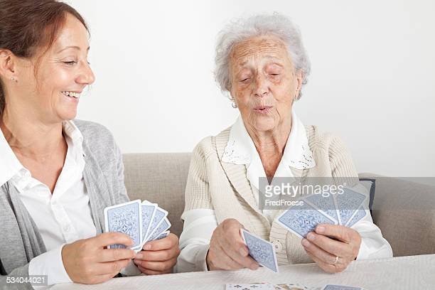 Senior woman with her home caregiver playing cards