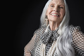 Portrait of a smiling senior woman with long gray hair against black background