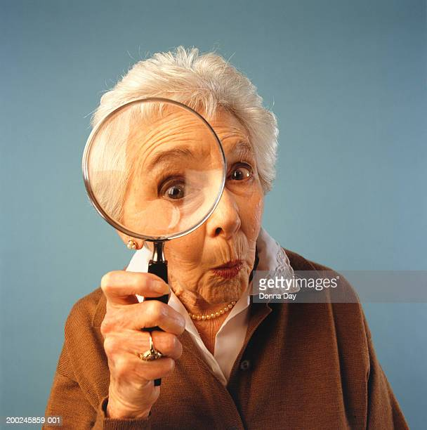 Senior woman with magnifying glass, (Portrait)