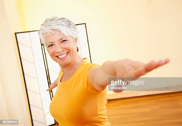 Senior woman with stretched arms, smiling, portrait