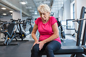 Elderly woman suffering from pain in leg and knee sitting on at gym. Senior woman at rehab club.