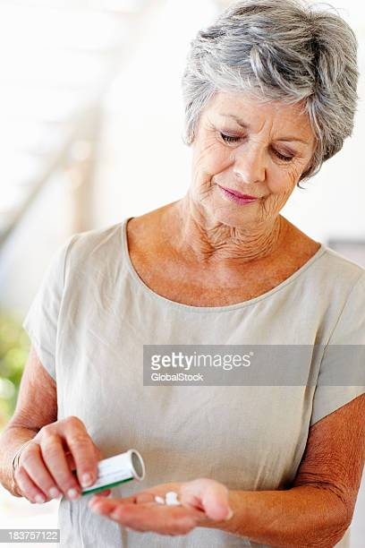 Senior woman with pills in her hand