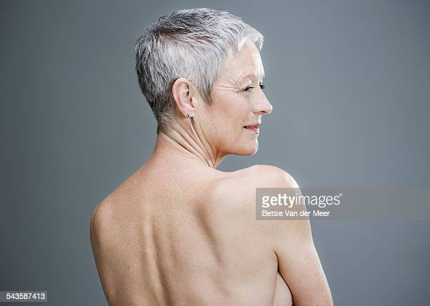 Senior woman with shirtless back turned to camera.