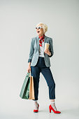 happy senior woman in jacket and sunglasses with shopping bags and coffee, isolated on grey