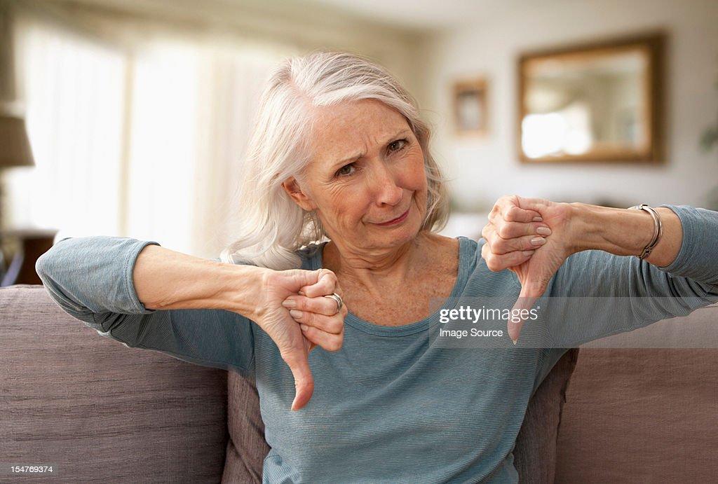 Senior woman with thumbs down : Stock Photo