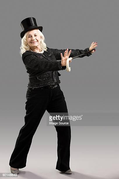Senior Mujer con sombrero de copa y caña