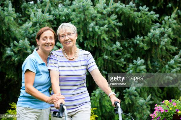 Senior woman with walker and caregiver