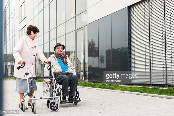 Senior woman with wheeled walker and senior man in wheelchair on pavement