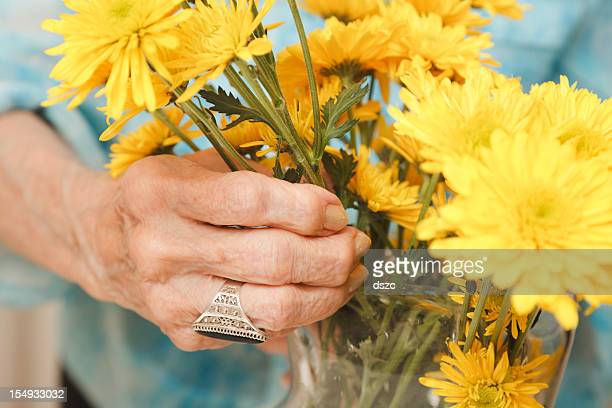 senior woman with yellow cut flowers