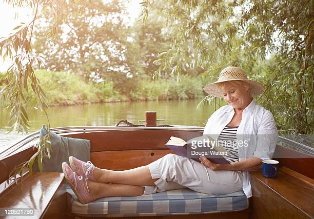 Senior woman woman reading book in vintage boat.