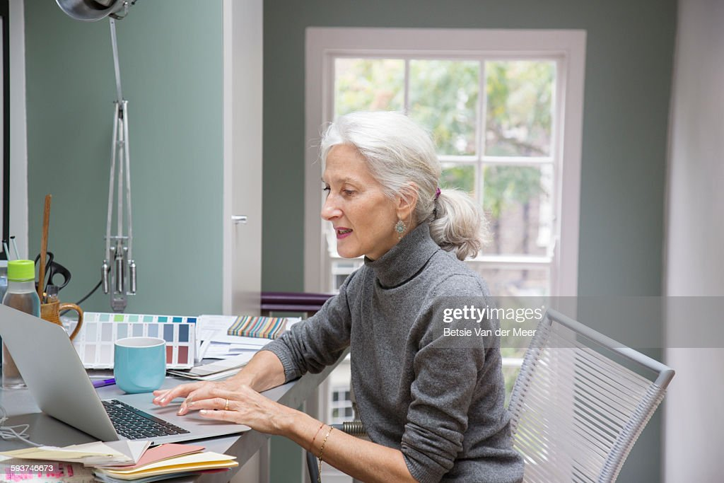 Senior woman working at desk at home office.