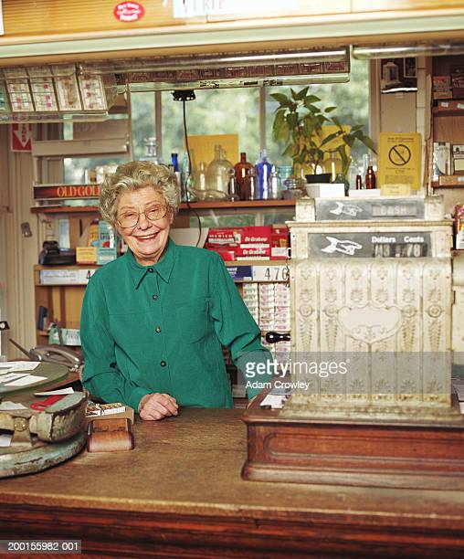 Senior woman working at general store, smiling, portrait