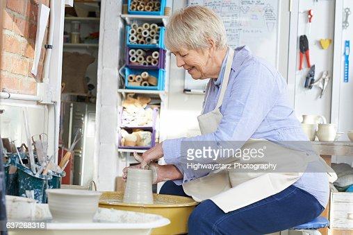 Senior Woman Working At Pottery Wheel In Studio : Stock Photo