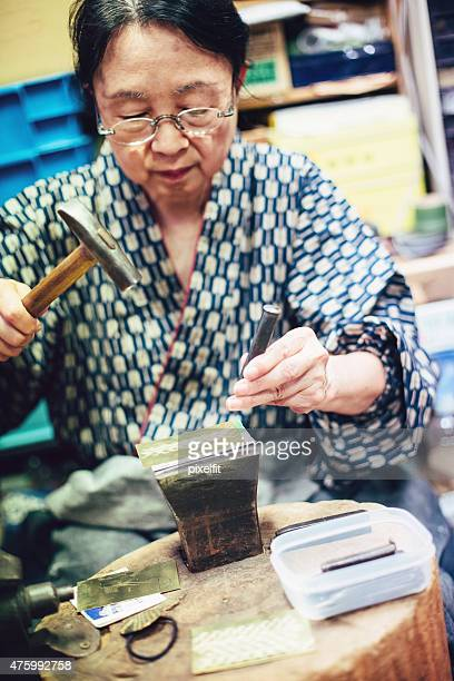 Femme âgée travaillant dans son atelier.