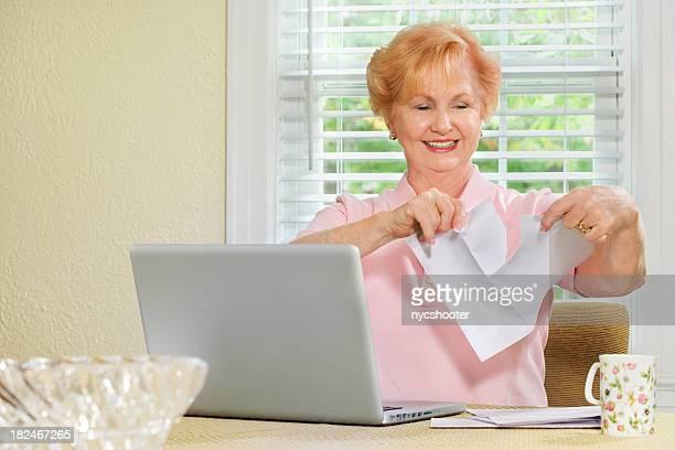 高齢者の女性のラップトップやペーパーレス