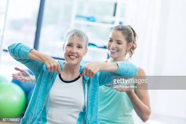 Senior woman works arms using barbells at the gym with her trainer