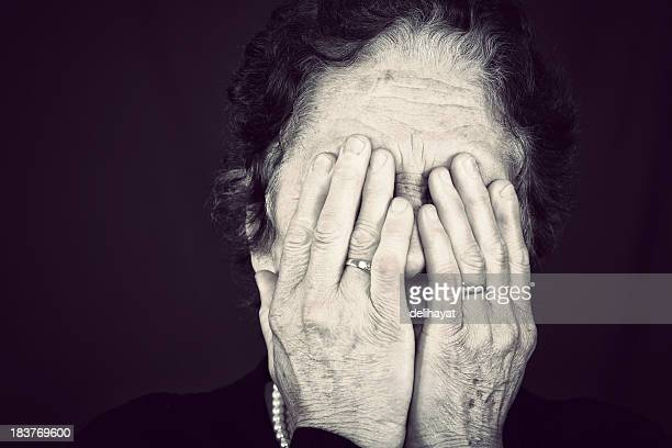 Senior woman worn hands covering face
