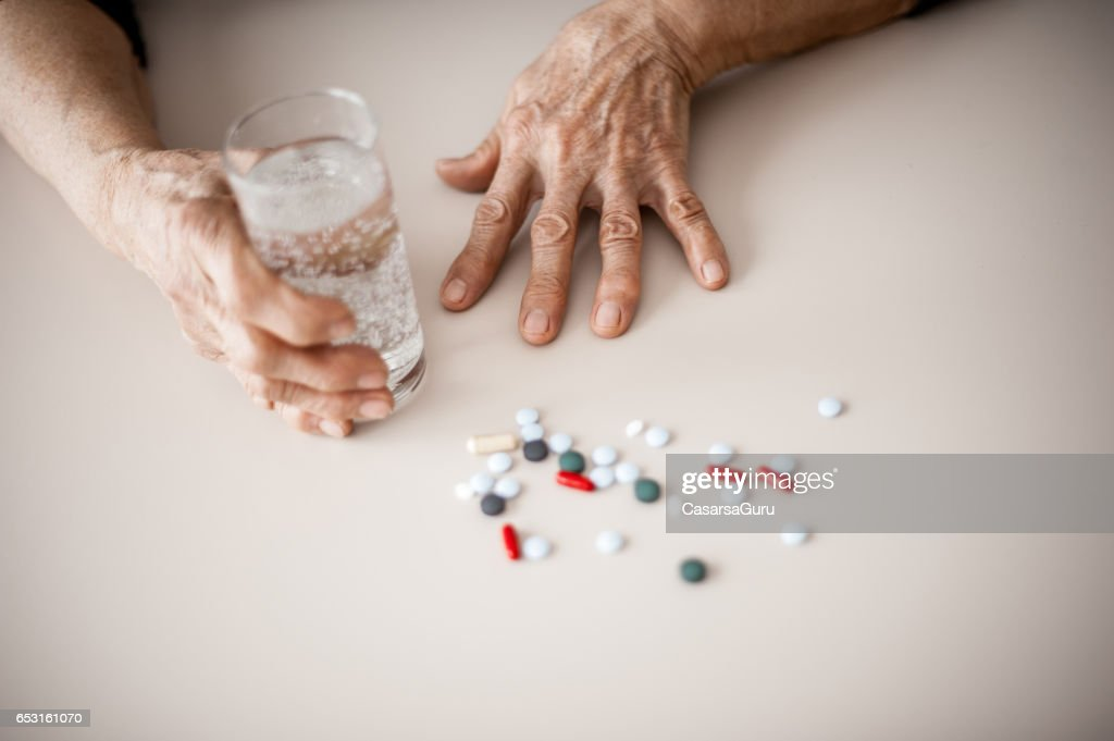 Senior Woman Wrinkled Hands Choosing Medicine To Take : Stock Photo