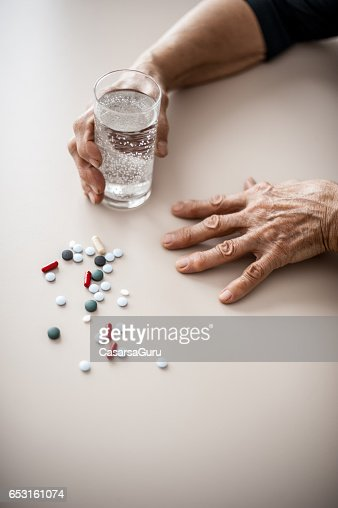 Senior Woman Wrinkled Hands Choosing Medicine To Take : Photo