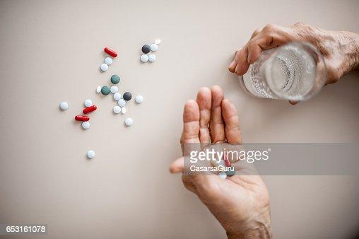 Senior Woman Wrinkled Hands Choosing Medicine To Take : Stock-Foto