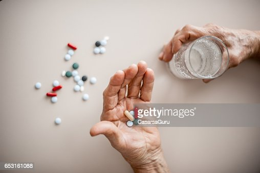 Senior Woman Wrinkled Hands Choosing Medicine To Take : Stock-Foto