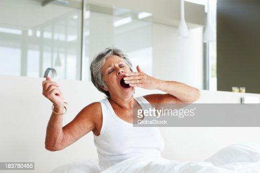 Senior woman yawning in bed