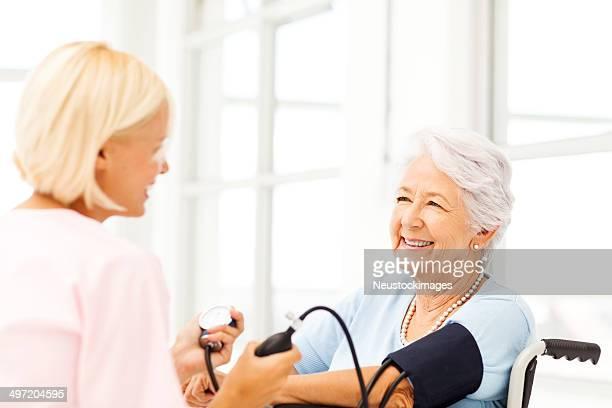 Senior Frau Blutdruck von Krankenschwester untersucht