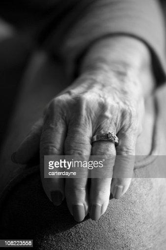 senior womans hand wearing wedding ring black and white