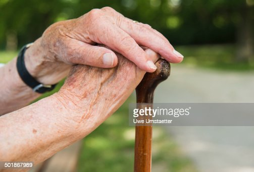 Senior woman's hands, holding walking stick