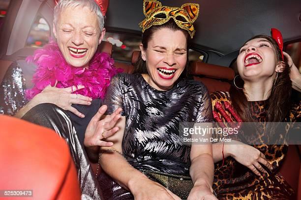 senior women and daughter laughing in car.