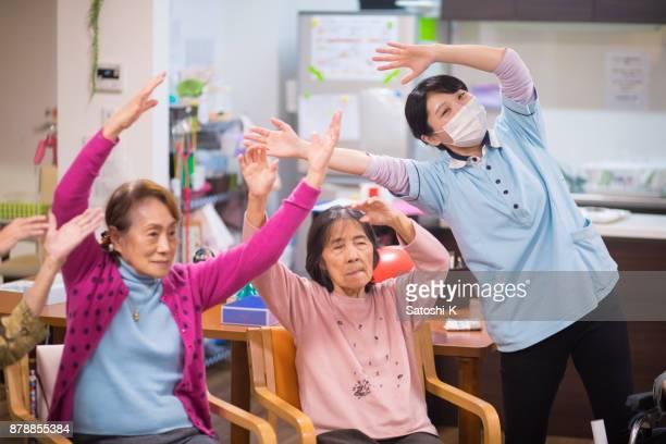 年配の女性と女性看護師のストレッチ