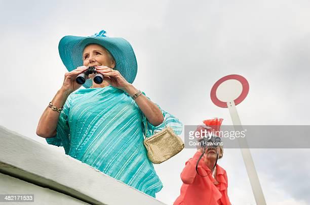 Senior women at races looking through binoculars