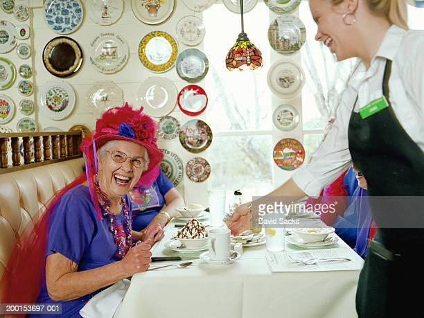 Senior women being served dessert in diner