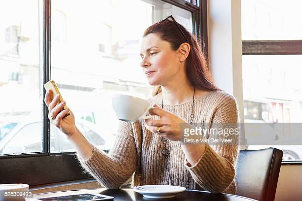senior women checks phone in cafe.