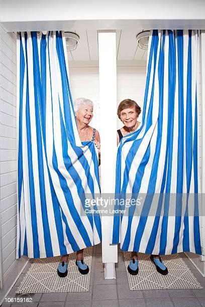 Senior women clutching shower curtains