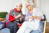 Senior women discussing while knitting at nursing home