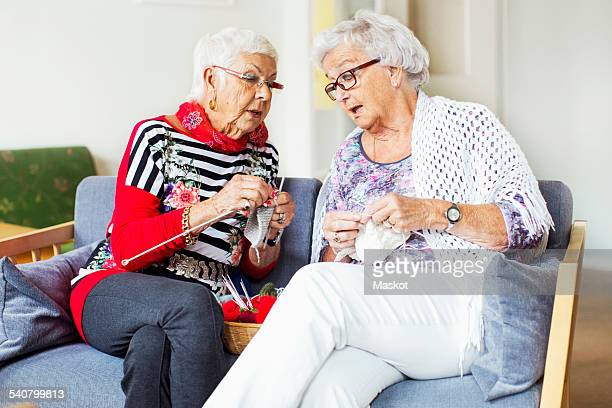 Senior women discussing while knitting at nursing home