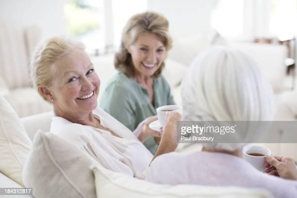 Femmes âgées boire du café sur le canapé-lit