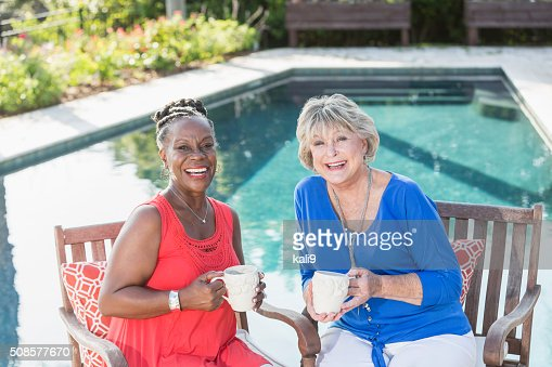 Senior women enjoying cup of coffee by swimming pool : Stockfoto