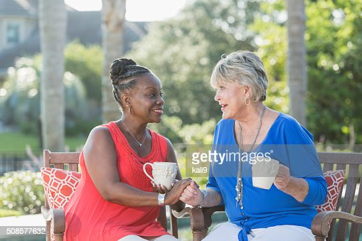 Senior women enjoying cup of coffee together, talking : Stockfoto